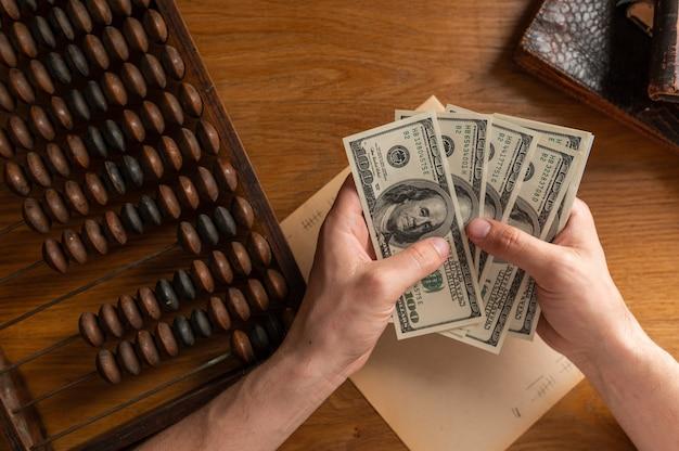 Mężczyzna ręce licząc rachunki w dolarach amerykańskich lub płacąc gotówką na tle pieniędzy