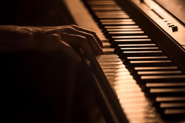 Mężczyzna ręce na klawiszach fortepianu zbliżenie piękne kolorowe tło, pojęcie działalności muzycznej