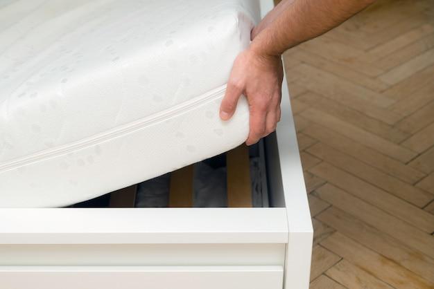 Mężczyzna ręce podnosząc materac w sypialni.