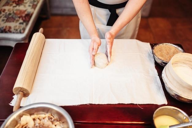 Mężczyzna ręce szefa kuchni i ciasto na drewnianym stole. domowe gotowanie strudla