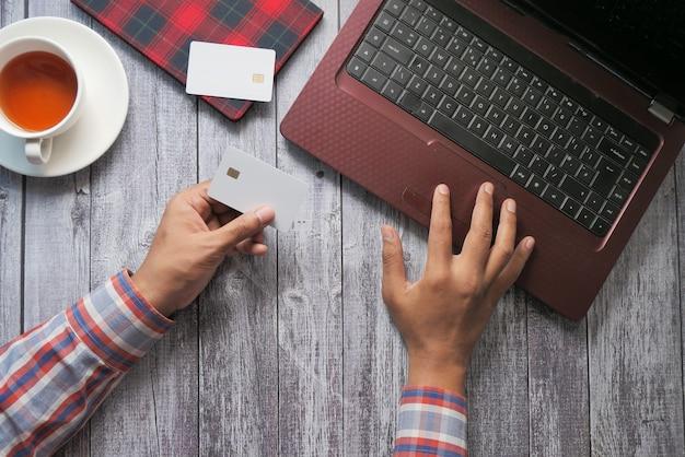 Mężczyzna ręce trzyma kartę kredytową i za pomocą klawiatury zakupy online, z góry na dół