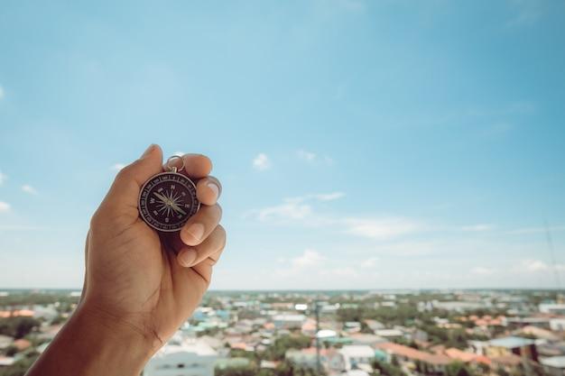 Mężczyzna ręce trzyma kompas na niebie