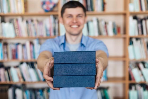 Mężczyzna ręce trzyma stos książek. mężczyzna wyciąga stos książek