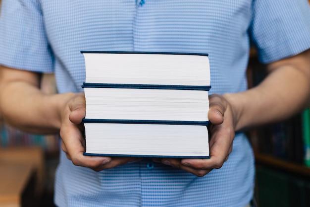 Mężczyzna ręce trzyma stos książek.