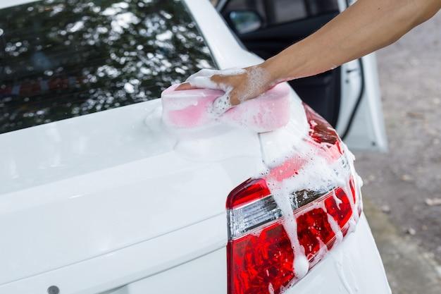 Mężczyzna ręce trzymać gąbkę do mycia białego samochodu
