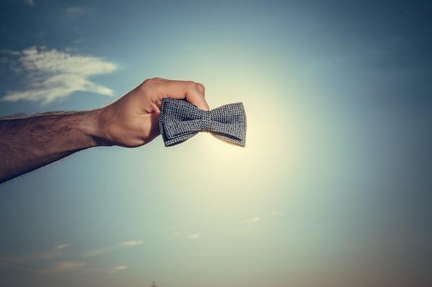 Mężczyzna ręce trzymając czarny krawat z niebieskim tle pochmurnego nieba. miejsce na tekst. koncepcja wakacje.