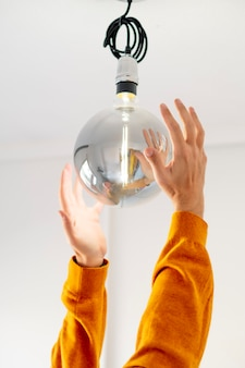 Mężczyzna ręce umieszcza gigantyczną nowoczesną żarówkę z białą ścianą