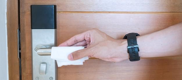 Mężczyzna ręcznie czyści cyfrową klamkę drzwi chusteczką do wycierania na mokro, ochronę przed koronawirusem lub chorobą koronawirusową (covid-19) w pomieszczeniu publicznym. czysta powierzchnia, styl życia, bezpieczna podróż i nowa normalna koncepcja