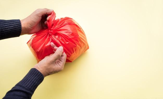 Mężczyzna ręcznie pakujący śmieci w czerwonej plastikowej torbie
