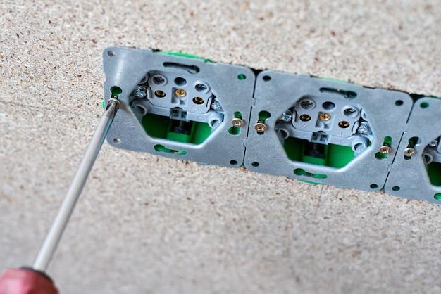Mężczyzna ręcznie zainstalować gniazdo elektryczne za pomocą śrubokręta w ścianie