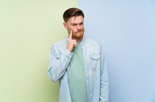 Mężczyzna redhead nad kolorowe ściany patrząc z przodu