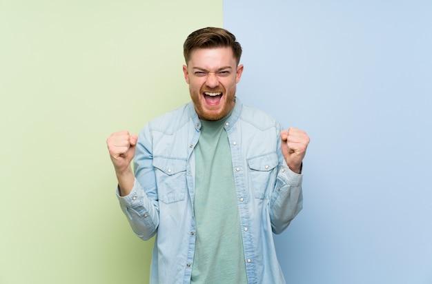 Mężczyzna redhead nad kolorowe ściany świętuje zwycięstwo w pozycji zwycięzcy