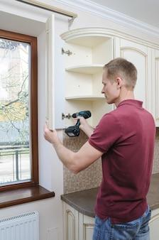 Mężczyzna reguluje zakrzywione drzwi szafki za pomocą śrubokręta