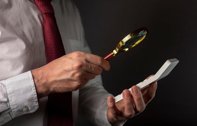 Mężczyzna ręka biznesmen trzymając kalkulator i lupę.