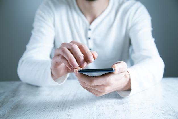 Mężczyzna ręka inteligentny telefon na stole
