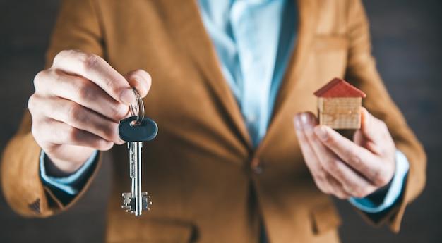 Mężczyzna ręka klucz i model domu w ciemności