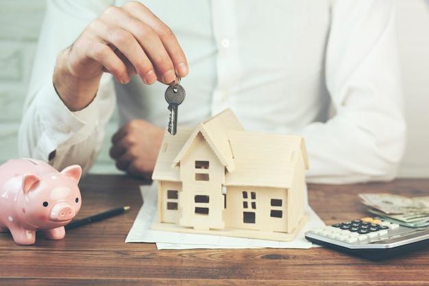 Mężczyzna ręka klucz i model domu