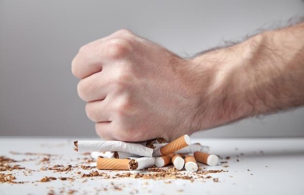 Mężczyzna ręka łamie papierosy. rzucanie palenia