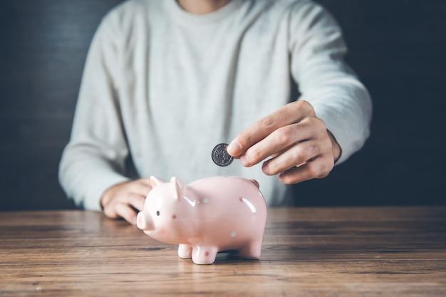 Mężczyzna ręka monety ze skarbonką na biurku