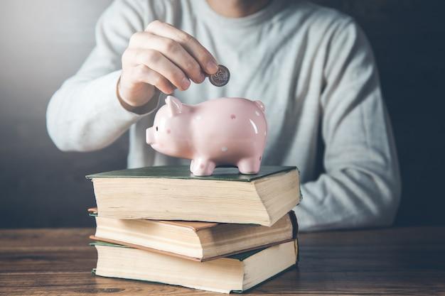 Mężczyzna ręka monety ze skarbonką na książki na biurku