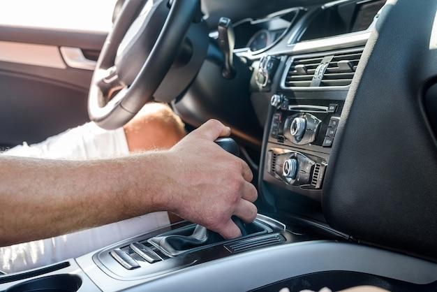 Mężczyzna ręka na przekładni wewnątrz samochodu. zamknij widok męskiej ręki z wnętrza samochodu