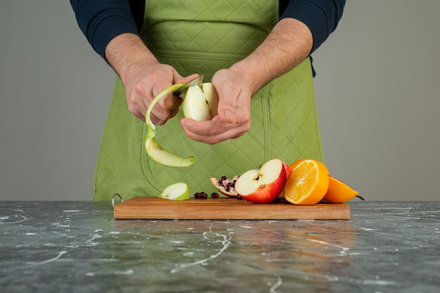Mężczyzna ręka obierania zielone jabłko na drewnianej desce na stole.