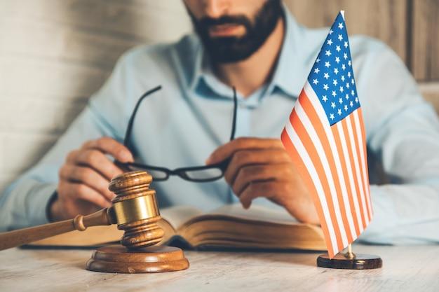 Mężczyzna ręka okulary z książką i sędzia na biurku