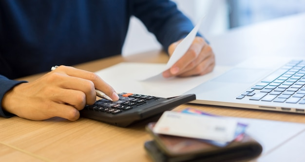 Mężczyzna ręka prasy kalkulator i myśl o długach rachunki miesięczne