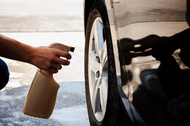 Mężczyzna ręka rozpyla samochodowego koło