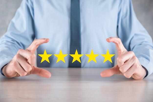 Mężczyzna ręka smartphone pokazano na pięć gwiazdek doskonałej oceny