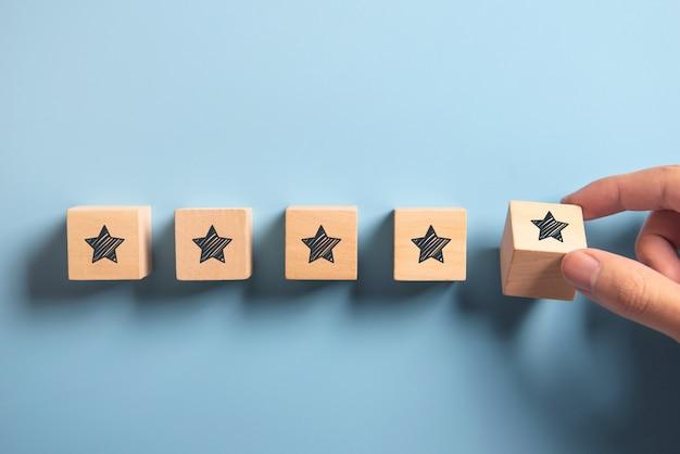 Mężczyzna ręka stawia drewnianego pięć gwiazdowego kształt na błękicie. najlepsze doskonałe usługi ocena koncepcji obsługi klienta