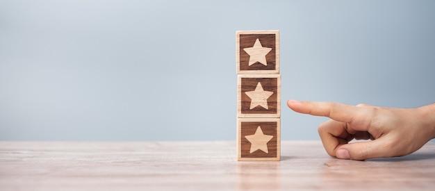 Mężczyzna ręka trzyma blok star. klient wybiera ocenę do recenzji użytkowników. ocena usług, ranking, ocena klientów, satysfakcja, ocena i koncepcja informacji zwrotnych