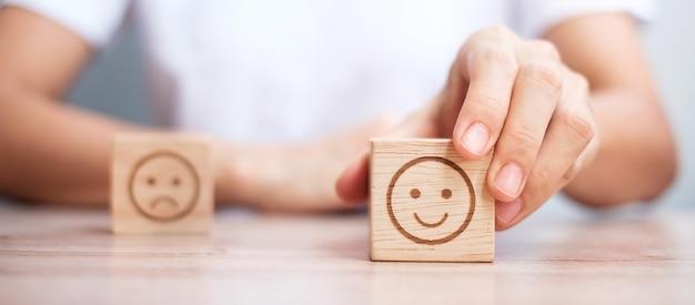 Mężczyzna ręka trzyma blok twarzy emocji. klient wybiera emotikon do recenzji użytkowników. ocena usług, ranking, ocena klientów, satysfakcja, ocena i koncepcja informacji zwrotnych