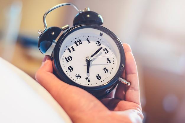 Mężczyzna ręka trzyma budzik na pobudkę o 7 rano rano obudź się na czas z efektem świetlnym w sypialni w ciepłym stylu vintage