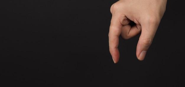 Mężczyzna ręka trzyma gesty i pusty znak, na białym na czarnym tle. kopiuj przestrzeń