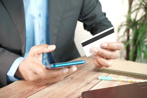 Mężczyzna ręka trzyma kartę kredytową i za pomocą inteligentnego telefonu zakupy online