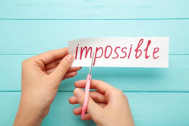 Mężczyzna ręka trzyma karty z tekstem niemożliwe. koncepcja sukcesu i wyzwania. widok z góry