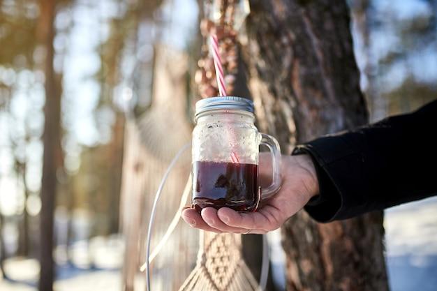 Mężczyzna ręka trzyma kieliszek grzanego wina na zimowy las