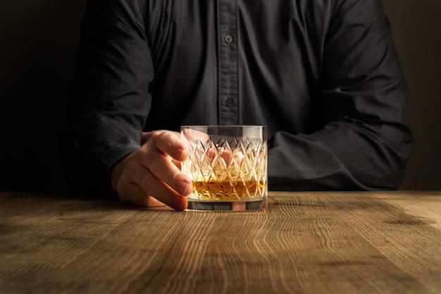 Mężczyzna ręka trzyma kieliszek whisky na drewnianym stole