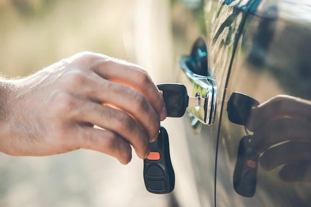 Mężczyzna ręka trzyma klucz i samochód