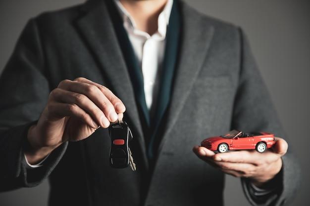 Mężczyzna ręka trzyma klucz z modelu samochodu