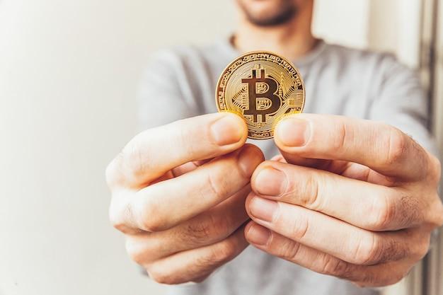 Mężczyzna ręka trzyma kryptowalutę złotą monetę bitcoin