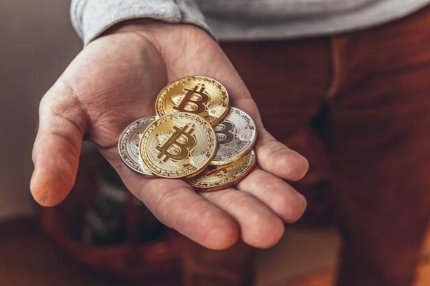 Mężczyzna ręka trzyma kryptowalutę złote i srebrne monety bitcoin