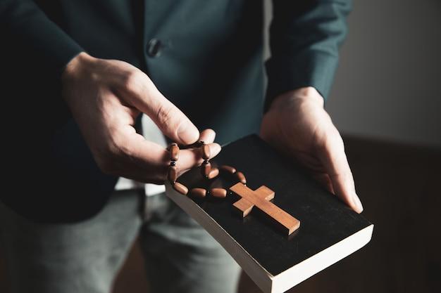 Mężczyzna ręka trzyma krzyż z biblią
