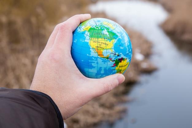 Mężczyzna ręka trzyma kulę ziemską planety.