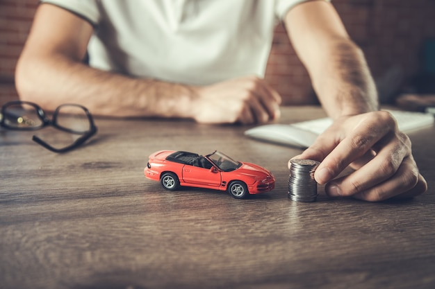Mężczyzna ręka trzyma model samochodu i monety