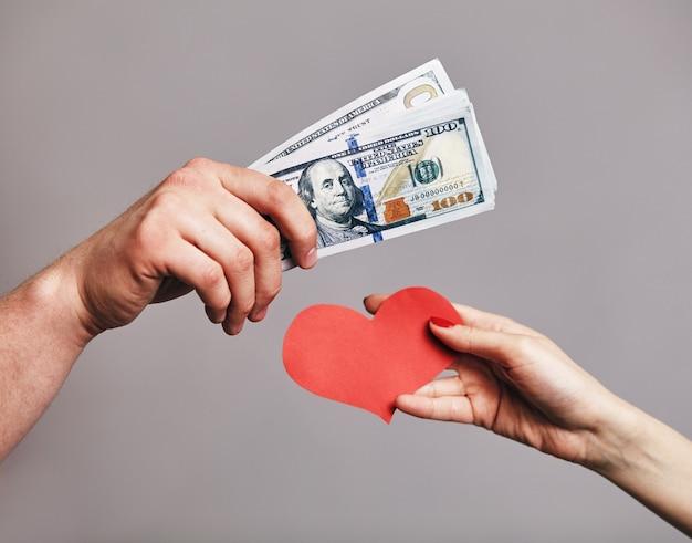 Mężczyzna ręka trzyma paczkę pieniędzy, próbując kupić czerwone serca od kobiecej ręki - kupowanie koncepcji miłości