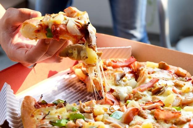 Mężczyzna ręka trzyma pizzę z pudełka