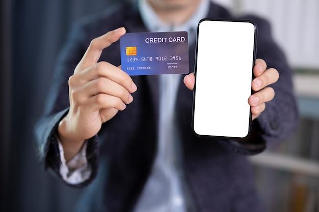 Mężczyzna ręka trzyma pustego ekranu smartphone i kredytową kartę