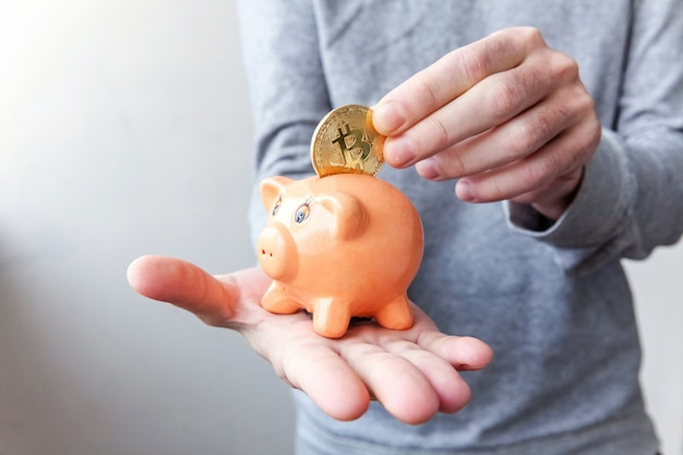 Mężczyzna ręka trzyma skarbonkę z kryptowalutą złotą monetą bitcoin